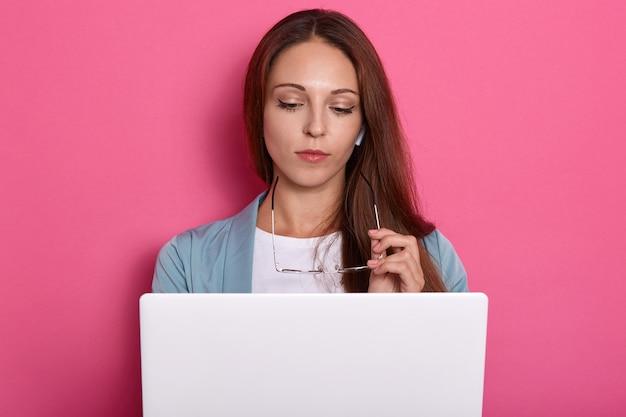Immagine orizzontale di posa adorabile affascinante astuta della giovane signora isolata sopra fondo rosa in studio