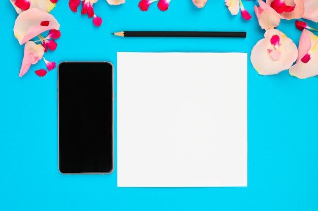 Immagine per il blog femminile. disposizione piana con fiori, taccuino, smartphone e matita su fondo di carta
