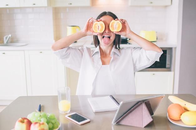 Immagine piacevole e divertente della ragazza che nasconde i suoi occhi con pezzi di arancia.