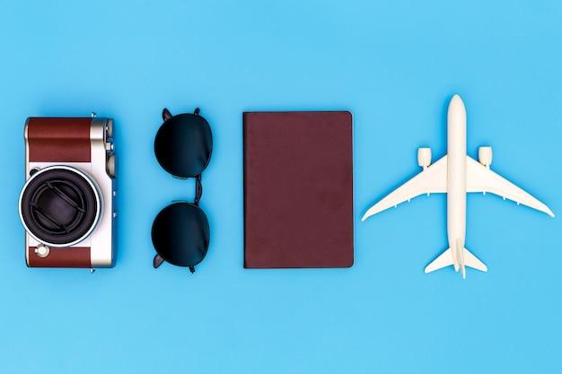 Immagine piatta laici di abbigliamento accessorio per pianificare il viaggio in vacanza su sfondo blu