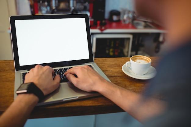 Immagine potata del cliente che scrive sul computer portatile al caffè
