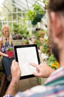 Immagine potata del giardiniere che per mezzo della compressa alla serra