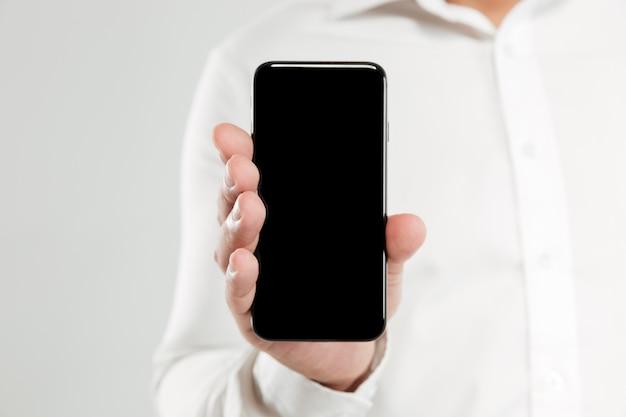 Immagine potata del giovane che mostra esposizione del telefono.