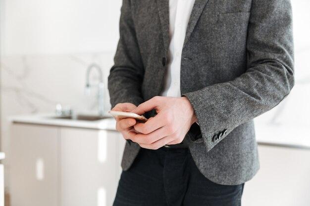 Immagine potata del messaggio di scrittura dell'uomo di affari in smartphone