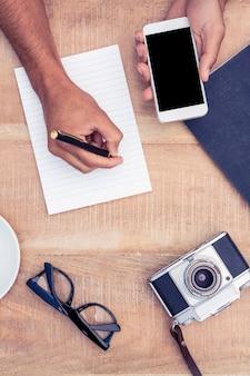 Immagine potata dell'uomo che scrive sul blocco note mentre tenendo lo smart phone dalla macchina fotografica e dagli occhiali sul tavolo