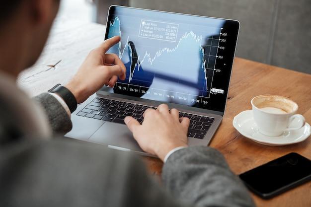 Immagine potata dell'uomo d'affari che si siede dalla tavola in caffè e che analizza gli indicatori sul computer portatile