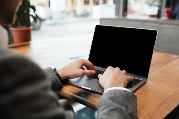 Immagine potata dell'uomo d'affari che si siede dalla tavola in caffè e che scrive in computer portatile