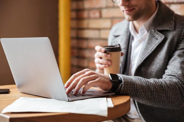 Immagine potata dell'uomo d'affari che si siede dalla tavola in caffè