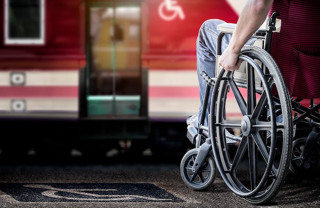 Immagine potata dell'uomo nella sua sedia a rotelle al binario della stazione ferroviaria