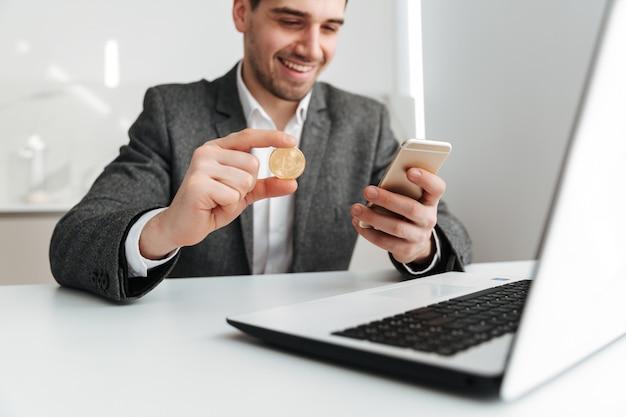 Immagine potata dell'uomo sorridente di affari che si siede dalla tabella