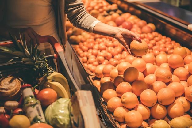 Immagine potata di bella donna che sceglie le arance.