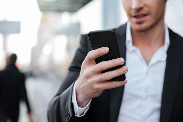 Immagine potata di giovane uomo d'affari felice che chiacchiera dal telefono.