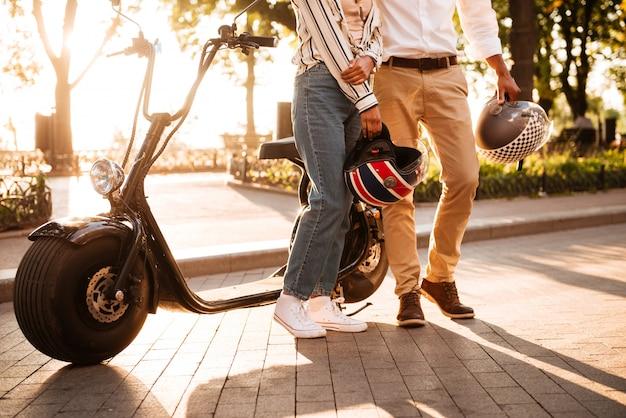 Immagine potata di giovani coppie africane che posano vicino alla motocicletta moderna in parco