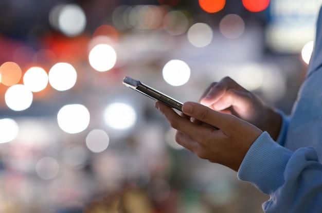 Immagine ravvicinata delle mani delle donne utilizzando smartphone di notte sulla strada dello shopping della città, ricerca o concetto di reti sociali, uomo hipster scrivendo un messaggio sms ai suoi amici
