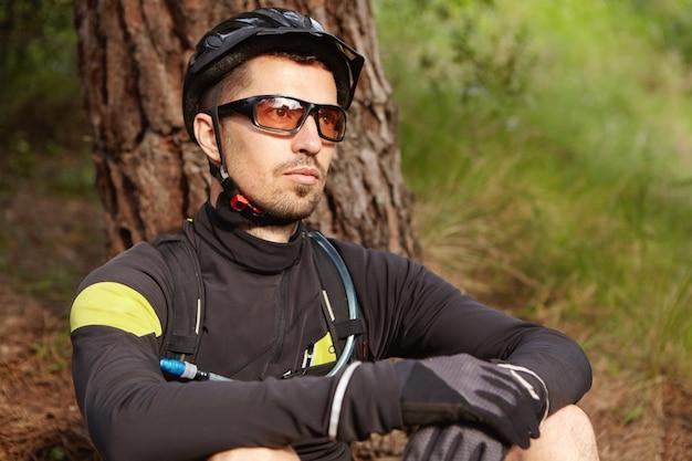 Immagine ravvicinata di bel ciclista con la barba rilassante dopo l'allenamento