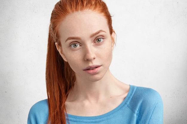 Immagine ravvicinata di bella donna dai capelli rossi dagli occhi verdi guarda con sicurezza, essendo sicuro in qualcosa, indossa un maglione blu, ha la pelle pura freskled