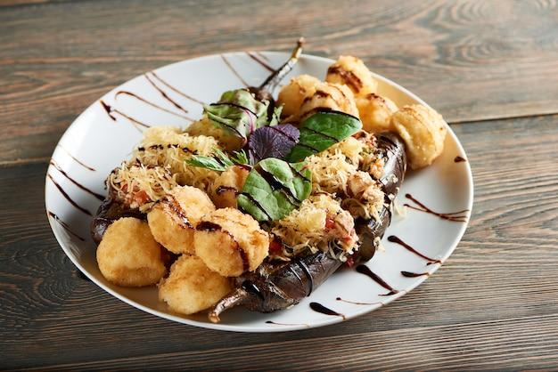 Immagine ravvicinata di deliziose palline di formaggio fritto servite con melanzane e basilico su un tavolo in legno bar ristorante pasto cena pranzo appetito affamato gustoso concetto di nutrizione.