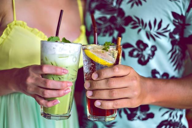 Immagine ravvicinata di giovani coppie sorridenti godersi i loro drink, facendo applausi alla fotocamera, matcha latte e limonata ai frutti di bosco, cocktail alla festa, colori vivaci tonica.