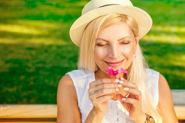 Immagine ravvicinata di una bella donna bionda matura che riposa al parco odorando il fiore