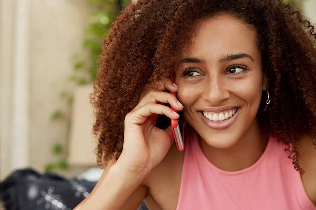 Immagine ravvicinata di una giovane donna allegra dall'aspetto piacevole con acconciatura afro, felice di sentire la voce del ragazzo tramite un moderno telefono cellulare, non si vede da molto tempo, si manca molto