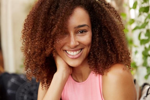 Immagine ravvicinata di una ragazza adolescente dalla pelle scura positiva ha un'acconciatura afro, vestita casualmente, ha un sorriso splendente, riposa al coperto con un amico intimo o un ragazzo, essendo di buon umore. persone, bellezza, etinicità