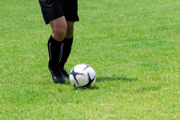 Immagine ravvicinata, i calciatori stanno gocciolando sull'erba.