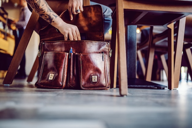 Immagine ritagliata dell'uomo d'affari che estrae la compressa della sua borsa. interno della caffetteria.