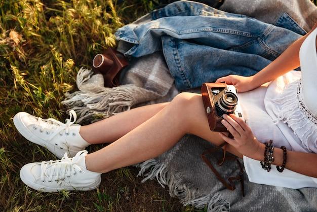 Immagine ritagliata della ragazza caucasica 20s in scarpe da ginnastica e vestito tenendo la fotocamera retrò, mentre è seduto sull'erba nel parco sotto il sole