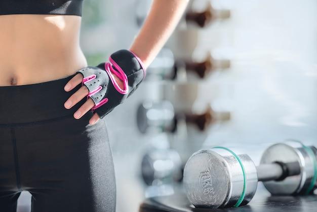 Immagine ritagliata di allenamento esercizio donna in palestra fitness con manubri