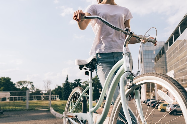 Immagine ritagliata di una giovane donna in jeans e una maglietta con una bicicletta