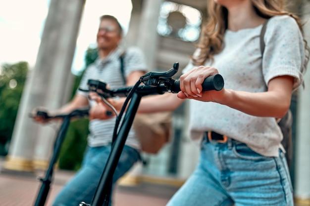 Immagine ritagliata di una ragazza affascinante e un ragazzo attraente su scooter elettrici.