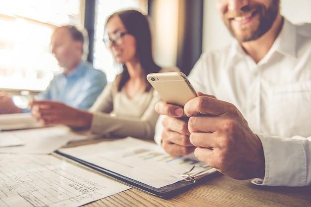 Immagine ritagliata di uomini d'affari belli utilizzando gadget.