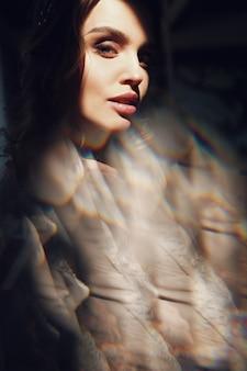 Immagine sfocata della donna in abito luminoso che guarda sopra la sua spalla