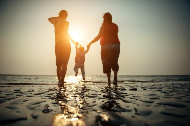 Immagine sfocata delle coppie della famiglia con il piccolo bambino contro il tramonto sul mare