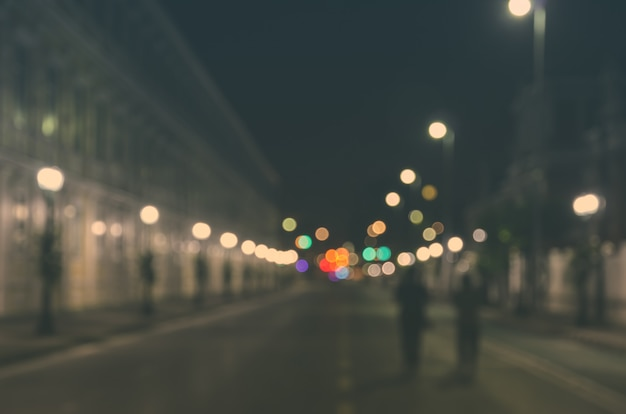 Immagine sfocata di persone che camminano attraverso una strada cittadina con auto vuota di notte