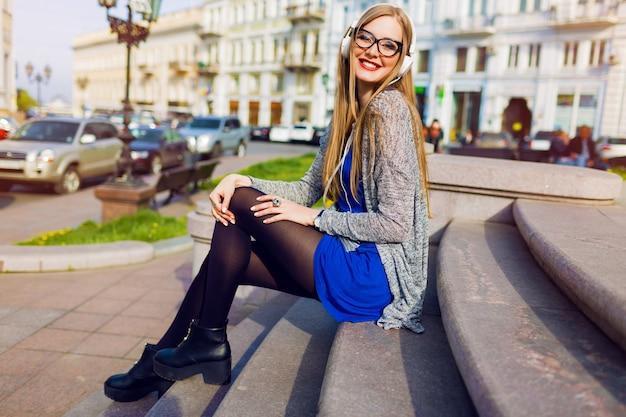 Immagine soleggiata di stile di vita di estate di donna bionda abbastanza giovane che ascolta la musica dalle cuffie, tenendo telefono cellulare, sedendosi sulla via, sognando. indossa un elegante vestito primaverile.