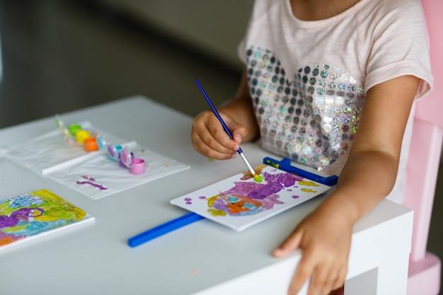 Immagine sveglia della pittura della bambina a casa.