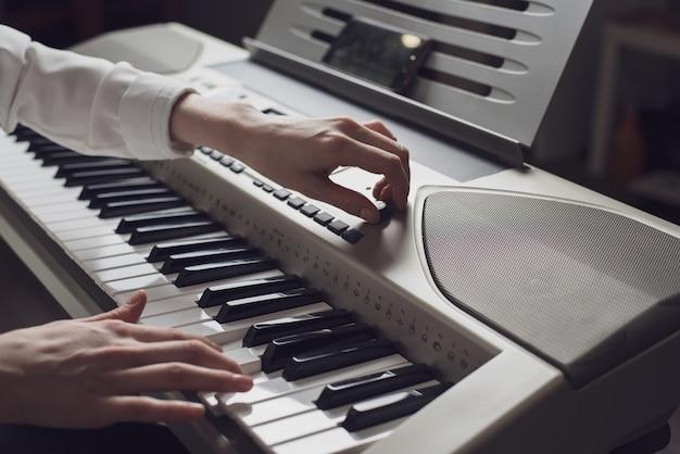 Immagine tonificata del primo piano delle mani femminili di synth sintonia