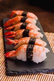 Immagine verticale dei sushi di nigiri su una stuoia di rotolamento di bambù tradizionale.