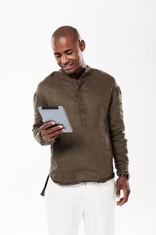 Immagine verticale dell'uomo africano sorridente che per mezzo del computer della compressa