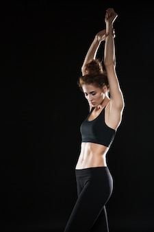 Immagine verticale della donna di forma fisica che si tiene per mano al di sopra