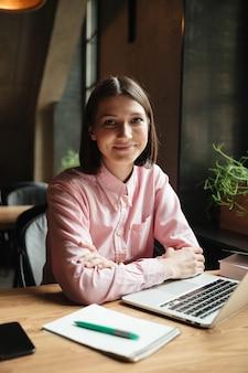 Immagine verticale della donna felice del brunette che si siede dalla tabella