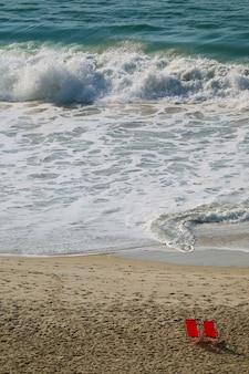 Immagine verticale delle onde che si infrangono nell'oceano con sedie a sdraio rosse sulla spiaggia di sabbia