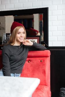 Immagine verticale di giovane donna seduta al tavolo