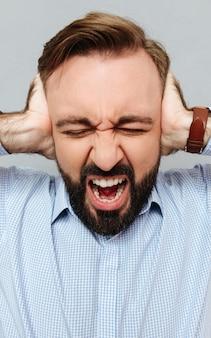 Immagine verticale di grida uomo barbuto in abiti d'affari