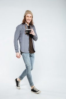 Immagine verticale di hipster tenendo la fotocamera retrò