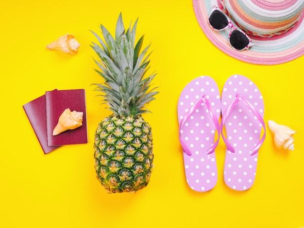 Immagine vista dall'alto di due passaporti, ananas fresco indossando occhiali da sole, ciabatte da spiaggia e cappello su uno sfondo giallo.
