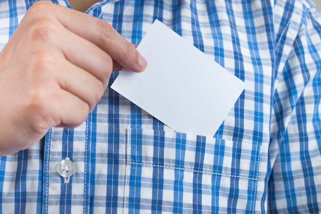 Immagini del primo piano di giovani uomini d'affari che selezionano biglietto da visita da una camicia di plaid blu