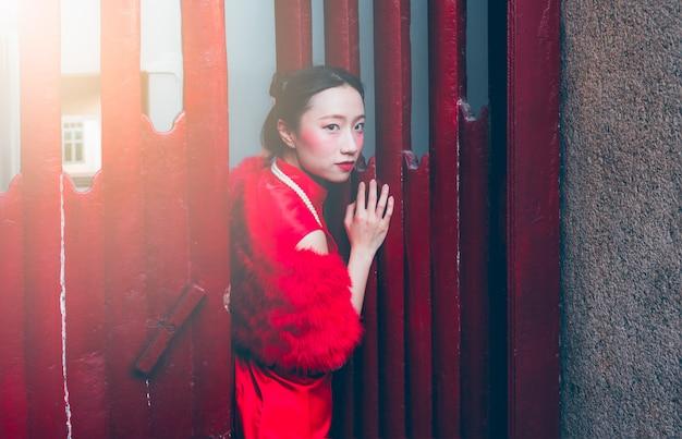 Immagini del ritratto della ragazza cinese che porta un vestito rosso di cheongsam che si leva in piedi su un portello di legno rosso.