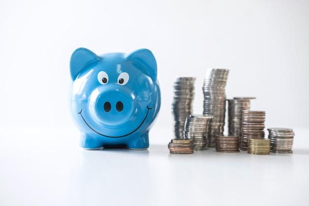 Immagini di impilare il mucchio di monete e salvadanaio sorridente blu per crescere e risparmiare con salvadanaio, risparmiando denaro per il piano futuro e il concetto di fondo pensione